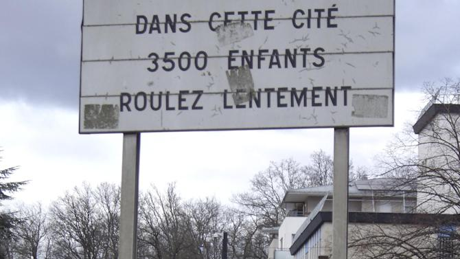 """In this photo taken Feb. 7, 2013, a road sign in the Paris district of Montfermeil reads, """"In this District, 3500 children, Slow Driving."""" In Montfermeil many residents don't speak French, delinquency soars, and the unemployment rate is an estimated 40 percent, nearly four times the national rate. The area's housing projects, burgeoning with immigrants, bear names like Cezanne, Picasso and Utrillo. But neither the great master's names, nor the idyllic images conjured by project's name, like Les Bosquets, or The Groves, captures the daily realities of the French-style ghetto. (AP Photo/Elaine Ganley)"""