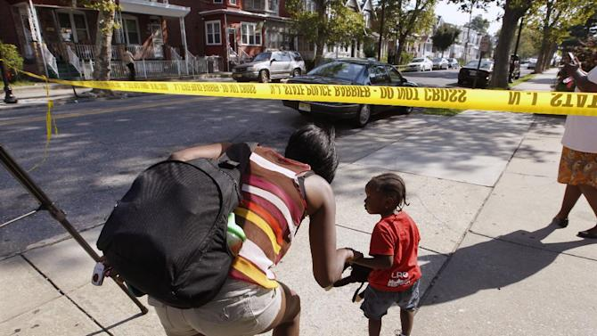 """Neighbors duck under police tape near 1415 Kaighn Ave.,  in Camden, N.J., Wednesday, Aug. 22, 2012.  Police say a New Jersey mother apparently decapitated her 2-year-old boy and put his head in the freezer of their home before she fatally stabbed herself. Chevonne Thomas, 33, called 911 just after midnight to say something had happened to her child and it """"sounded like she had done it,"""" said Jason Laughlin, a spokesman for the county prosecutor's office. Officers found Zahree Thomas' body on the first floor of the Camden home and the boy's head in the freezer. The mother stabbed herself in the neck with a kitchen knife and died, Laughlin said. (Photo/Mel Evans)"""