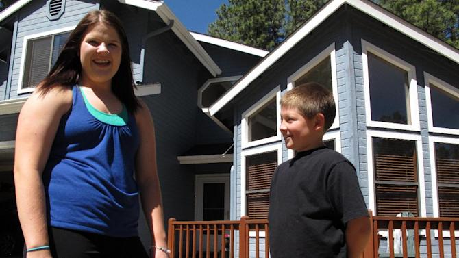 In this photo taken Thursday, June 7, 2012, Colleen Knaggs, 18, talks about her fruitless efforts to find a summer job, from her home in Flagstaff, Ariz. Instead, Knaggs will be babysitting her younger brother, Matthew Knaggs, 10,  right. Once a rite of passage to adulthood, summer jobs for teens are disappearing. Fewer than 3 in 10 American teenagers now hold such positions as running cash registers, mowing lawns or busing tables in the months from June to August. The decline has been particularly sharp since 2000, with employment for the 16-19-year olds falling to the lowest level since World War II.   (AP Photo/Felicia Fonseca)