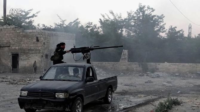 In this Thursday, June 20, 2013 citizen journalism image provided by Aleppo Media Center AMC, which has been authenticated based on its contents and other AP reporting, a Syrian rebel fires a heavy machine gun towards Syrian soldiers loyal to Syrian President Bashar Assad in Aleppo, Syria. _ The Syrian rebels' record in handling tens of millions of dollars in U.S. aid so far suggests major challenges ahead for any delivery of American weapons and ammunition. Food, medicine and other life-saving supplies regularly run into long delays because of bickering among rebel factions, U.S. officials say. (AP Photo/Aleppo Media Center AMC)
