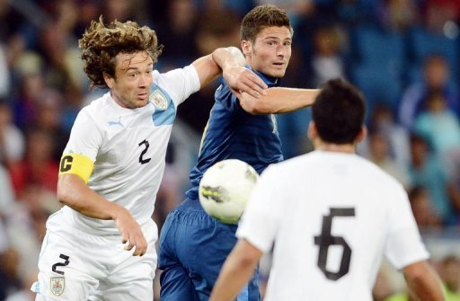 French forward Olivier Giroud (C) clashes with Uruguayan defender Diego Lugano (L)