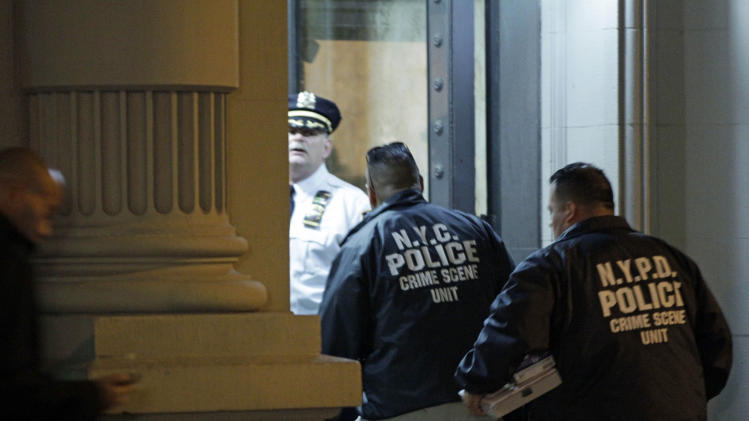 Crime scene unit officials enter the luxury Manhattan apartment building where police say a nanny stabbed two small children to death in a bathtub and then stabbed herself in New York, Thursday, Oct. 25, 2012. Police say the children's mother found the scene after returning home with another child. (AP Photo/Kathy Willens)