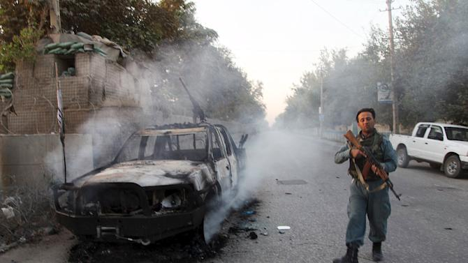 An Afghan policeman patrols next to a burning vehicle in Kunduz, Afghanistan