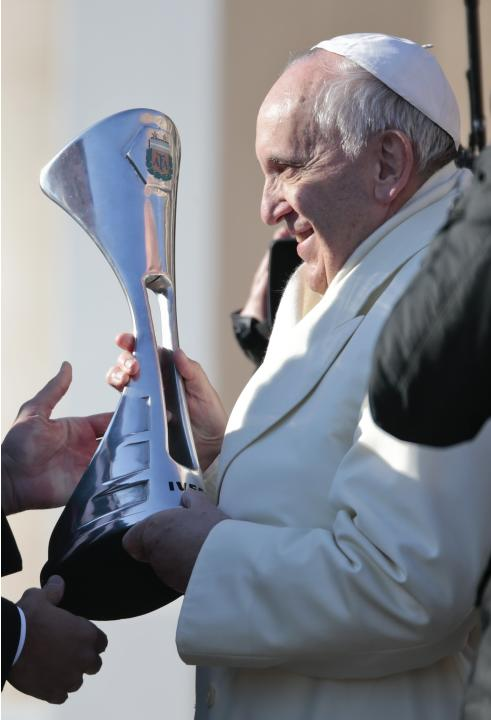 Pope Francis is presented with the replica of the trophy that Argentinian soccer team San Lorenzo won in the Argentinian soccer championship, during the Wednesday general audience in Saint Peter's