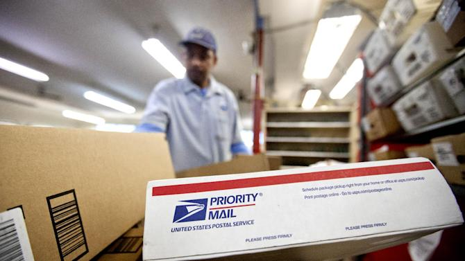 FILE - This Feb. 7, 2013 file photo shows packages waiting to be sorted in a Post Office in Atlanta. Regulators on Tuesday, Dec. 24, 2013, approved a price hike of 3 cents for a first-class stamp, bringing the charge to 49 cents a letter in an effort to help the Postal Service recover from severe mail decreases brought on after the 2008 economic downturn.(AP Photo/David Goldman, File)