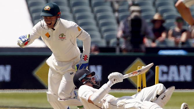 New Zealand's Mitchell Santner falls over after being stumped by Australia's wicketkeeper Peter Nevill for 45 runs during the third day of the third cricket test match at the Adelaide Oval, in South Australia