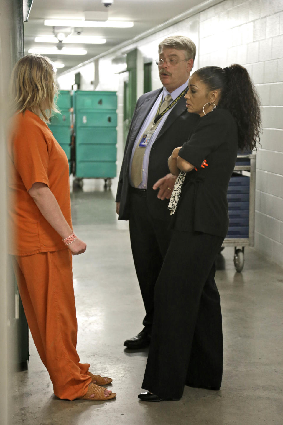 Kathryn Griffin Grinan, right, and Wayne Heintze, center,director of reentry services for the Harris County Sheriff's Office, talk with an inmate outside her cell Tuesday, June 4, 2013, in Houston. The inmate was arrested soon after being paroled and leaving Griffith's prostitution rehabilitation program. (AP Photo/Pat Sullivan)
