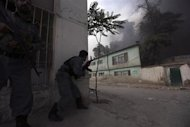 Afghan policemen take up position as smoke billows from the site of an explosion in Kabul May 24, 2013. Several large explosions rocked a busy area in the centre of the Afghan capital, Kabul, on Friday with Reuters witnesses describing shooting in the area. REUTERS/Omar Sobhani
