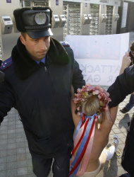 A police officer detains a topless woman protesting against alleged attempts to legalize prostitution during the Euro 2012 in Ukraine prior to the final draw for the Euro 2012 soccer tournament in Kiev, Ukraine, Friday, Dec. 2, 2011. Ukrainian women's rights activists staged a topless demonstration at Kiev's Olympic Stadium to protest what they say are attempts to legalize prostitution during the 2012 European Championship. (AP Photo/Ferdinand Ostrop)