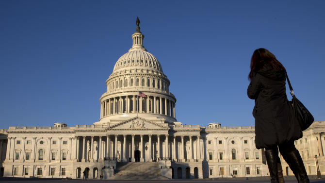 FILE - In this Dec. 31, 2013, file photo, a woman looks at the U.S. Capitol in Washington. After last fall's tumultuous, bitterly partisan debt ceiling and government shutdown battles, a sense of fiscal fatigue seems to be setting in among many Washington policymakers as President Barack Obama prepares for his fifth State of the Union address later this month. (AP Photo/Jacquelyn Martin, File)