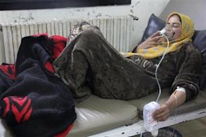 A woman breathes through an oxygen mask inside a field hospital in Kfar Zeita village in the central province of Hama