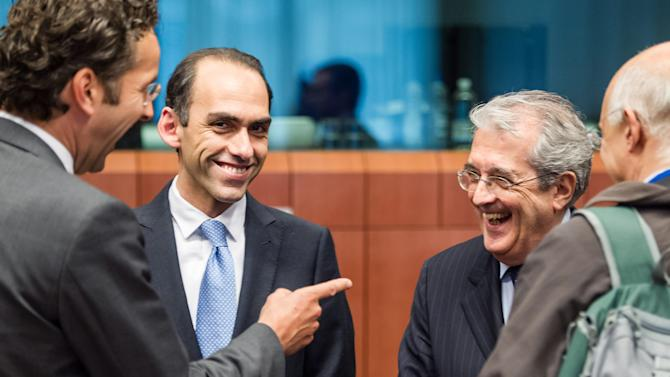 Italy's Finance Minister Fabrizio Saccomanni, right, smiles as he talks with Eurogroup President Jeroen Dijsselbloem, left, and Cyprus' Finance Minister Haris Georgiades, 2nd left, at the start of an Eurogroup meeting at the EU Council in Brussels on Monday, May 13, 2013. (AP Photo/Geert Vanden Wijngaert)