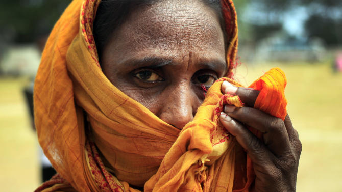 A woman covers her nose to block out the smell of bodies as she leaves the morgue which is temporarily housing bodies pulled out of the rubble from the garment factory collapse, Sunday, May 5, 2013 in Savar, near Dhaka, Bangladesh. Police said more than 600 bodies have now been recovered from the ruined building on Sunday and the grim recovery work continues. (AP Photo/Wong Maye-E)
