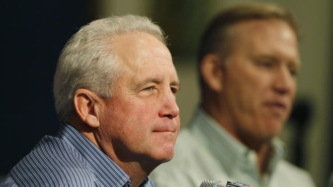 Denver Broncos head coach John Fox, front, listens as John Elway, the team's executive vice president of football operations, responds to questions about the team's loss to the Baltimore Raens in an AFC playoff game during a news conference at the team's headquarters in Englewood, Colo., on Monday, Jan. 14, 2013. (AP Photo/David Zalubowski)