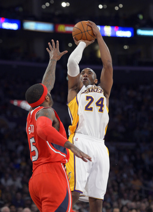 Los Angeles Lakers guard Kobe Bryant, right, puts up a shot as Atlanta Hawks forward Josh Smith defends during the first half of their NBA basketball game, Sunday, March 3, 2013, in Los Angeles. (AP P