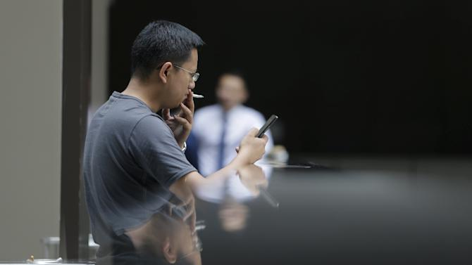 A man looks at his mobile phone as he smokes a cigarette outside an office building in Beijing