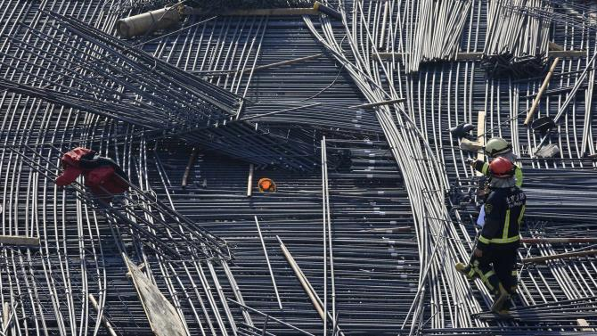 Rescue workers walk next to a helmet left on the steel bars at Tsinghua High School after a construction site for the school's new stadium collapsed, in Beijing