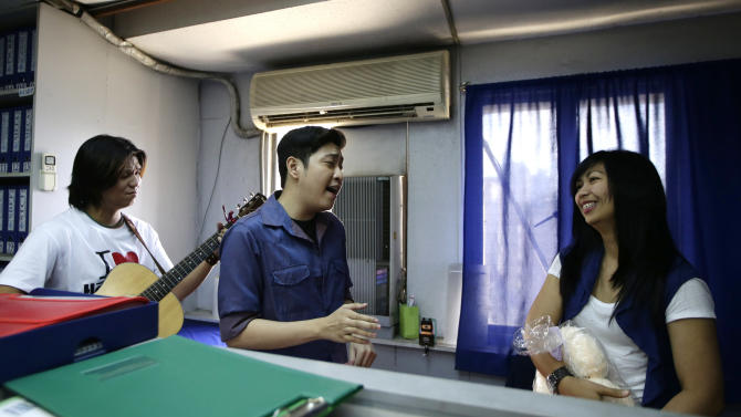 Rose Natividad, right, reacts as a singer, hired by her partner who is working for a cruise liner overseas, serenades her as a surprised Valentine's Day gift to her at her office in Manila, Philippines Thursday Feb. 14, 2013. The unique surprise serenade service, which includes love songs, a cuddly teddy bear, and a video recording of the romance-by-proxy event that is shipped to the client abroad, is played out in restaurants, offices and homes across the Philippines on Valentine's Day. (AP Photo/Bullit Marquez)
