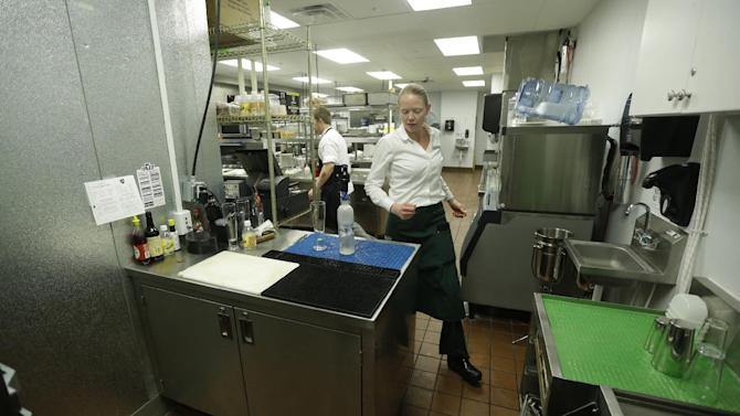 "Manager Lindsay Pitts walks around the bar  which is beyond the view of patrons in the kitchen of La Jolla Groves Restaurant Monday, Feb. 26, 2013, in Salt Lake City. Utah lawmakers are considering repealing a law that requires restaurants to mix alcoholic drinks out of view from patrons. Commonly known as ""Zion curtains,"" the mandate went into effect for restaurants in 2010 as part of a compromise when lawmakers lifted a mandate for bars to operate as members-only social clubs. The rule does not apply to restaurants that opened before 2010. A House committee is expected to discuss the bill Wednesday. Restaurant owners and tourism officials say the law is unnecessary and hinders tourism. But some lawmakers say that removing the mandate could encourage underage drinking and influence customers to drink too much. (AP Photo/Rick Bowmer)"