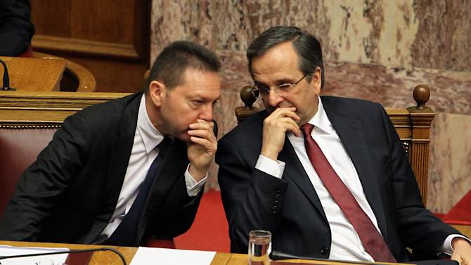 Greece's Prime Minister Antonis Samaras, right, speaks to Finance Minister Yannis Stournaras during a parliament meeting for vote on 2013 country's budget in Athens, Sunday, Nov. 11, 2012. Greece's lawmakers were set today to pass next year's austerity budget, extending tough spending cuts measures that have already left Greeks struggling as the country tries to slash its debts and pull itself out of a severe recession.(AP Photo/Thanassis Stavrakis)
