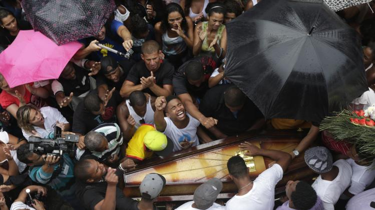 Relatives and friends of Douglas Rafael da Silva Pereira, 25, mourn during his burial in Rio de Janeiro