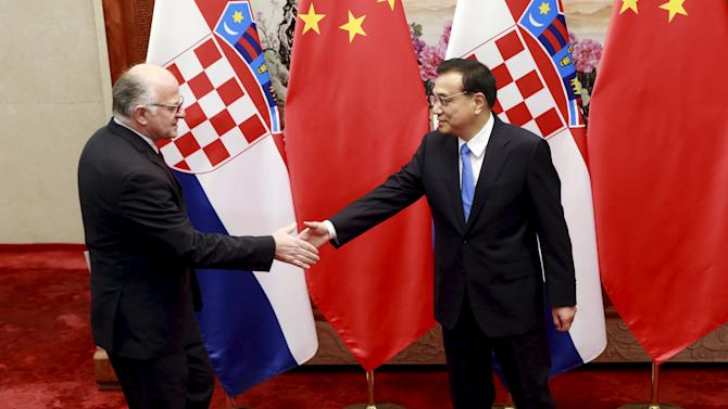 Josip Leko shakes hands with Li Keqiang during their meeting on the sidelines of the 4th Meeting of Heads of Government of China and Central and Eastern European Countries, at the Great Hall of the People in Beijing