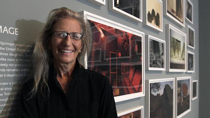 """Annie Leibovitz stands near some of her work before the opening of her exhibition at the Wexner Center for the Arts Friday, Sept. 21, 2012, in Columbus, Ohio. Leibovitz's exhibition features work from her """"Master Set,"""" an authoritative edition of 156 images. (AP Photo/Jay LaPrete)"""