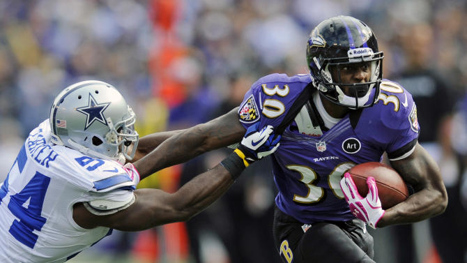 Baltimore Ravens running back Bernard Pierce, right, tries to outrun Dallas Cowboys inside linebacker Bruce Carter in the first half of an NFL football game in Baltimore, Sunday, Oct. 14, 2012. (AP Photo/Nick Wass)