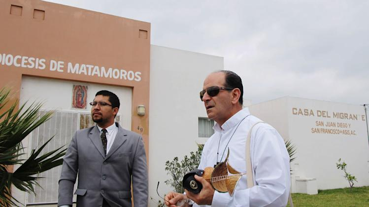 The Rev. Alejandro Solalinde, right, a Catholic priest visiting from southern Mexico, stands outside the migrant shelter in Matamoros, Mexico on April 8, 2013. After gunmen kidnapped 15 people from the shelter it began encouraging migrants to go into the streets during the day to become more difficult targets for organized crime. (AP Photo/Christopher Sherman)