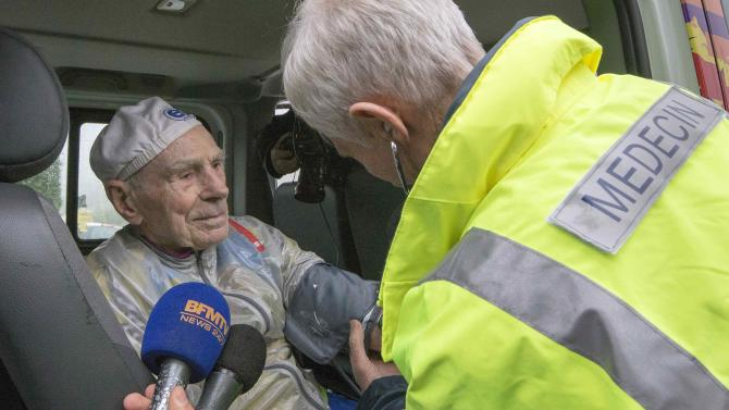 A doctor performs a medical check after French cyclist Robert Marchand climbed the Robert Marchand pass, in the Ardeche mountains, to celebrate his birthday near Saint-Felicien