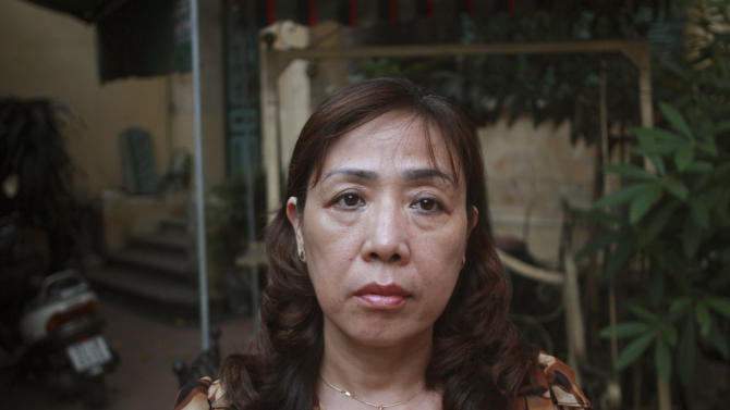 In this photo taken Monday, June 17, 2013, lawyer Nguyen Thi Duong Ha stands in the courtyard of her home in downtown Hanoi, Vietnam. Her husband Cu Huy Ha Vu is entering the fourth week of a prison hunger strike to protest alleged poor treatment. Vu was jailed after suing the prime minister and calling for multiparty democracy. His strike comes amid an intensifying crackdown on dissident, and illustrates how the government's most outspoken critics speak out despite threats to their health and safety. (AP Photo/Mike Ives)