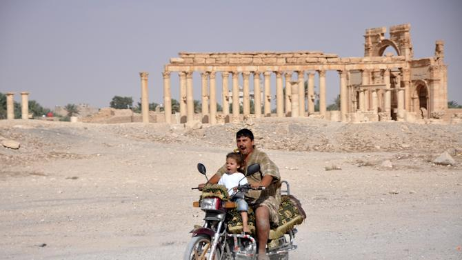 A man rides a motorcycle with a child in the historical city of Palmyra