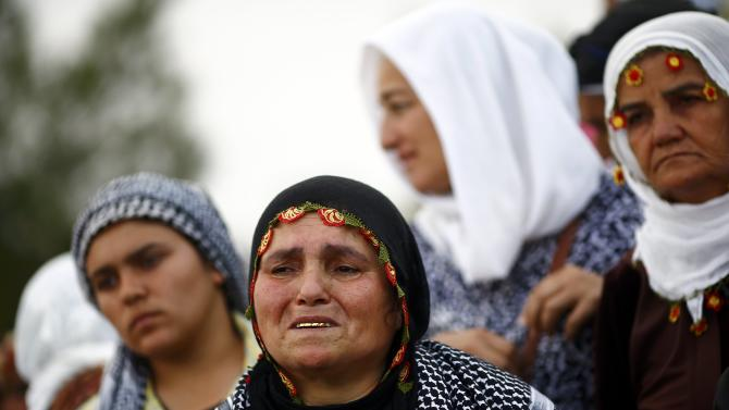 Turkish Kurdish women mourn during the funeral of Kurdish fighters killed during clashes against Islamic State in Syrian town of Kobani, at a cemetery in the southeastern town of Suruc