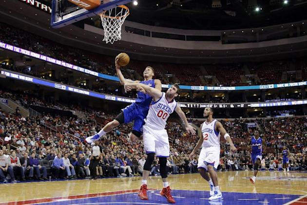 Los Angeles Clippers' Blake Griffin, left, goes up for a shot as Philadelphia 76ers' Spencer Hawes defends during the first half of an NBA basketball game, Monday, Dec. 9, 2013, in Philadelphi