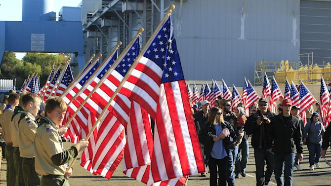 An honor guard of boy scouts from the local area and Michigan welcome visitors for the christening of the Navy's newest nuclear powered aircraft carrier USS Gerald R. Ford at the shipyard in Newport News, Va., Saturday, Nov. 9, 2013. Former President Ford's daughter Susan Ford Bales will christen the ship. (AP Photo/Steve Helber)