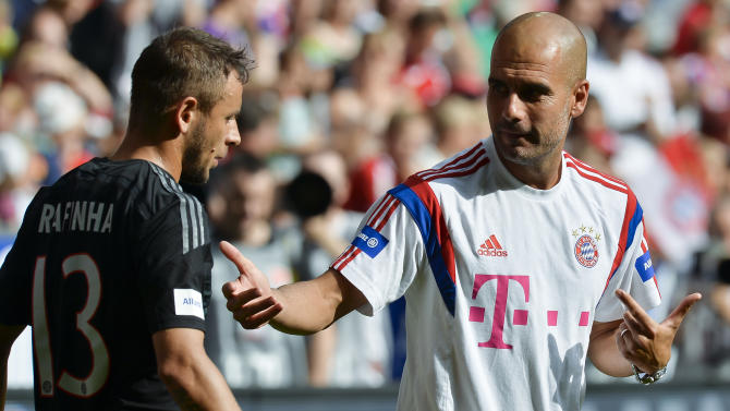 Bayern Munich's coach Pep Guardiola (R) talks to defender Rafinha (L) during a training session at the Allianz Arena stadium in Munich, southern Germany, on August 9, 2014