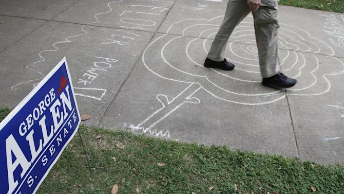 A voter walks past a campaign sign and over some drawings as he prepares to vote in the Republican primary at a school in Richmond, Va., Tuesday, June 12, 2012. (AP Photo/Steve Helber)
