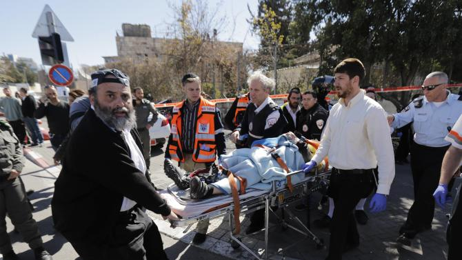 Israeli medics and a policeman evacuate an injured person from the scene of an attack in Jerusalem