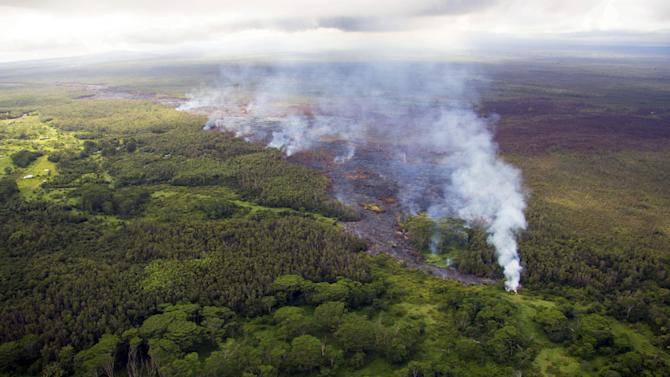 This Oct. 22, 2014 photo provided by the United States Geological Survey shows the front of a lava flow with numerous smoke plumes arising from active breakouts burning vegetation at the flow margin, near the town of Pahoa on the Big Island of Hawaii. The growing stream of lava threatening homes is expanding and speeding up as it heads toward the small rural town. Officials say the lava advanced nearly 460 yards from Thursday morning to Friday, Oct. 24, 2014. (AP Photo/U.S. Geological Survey)