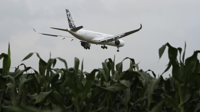 An Airbus A350XWB flies over a corn field while preparing to land during a demo flight at Noi Bai airport in Hanoi
