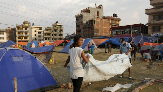 People displaced by the April 25 earthquake pack up their tent in Kathmandu, Nepal