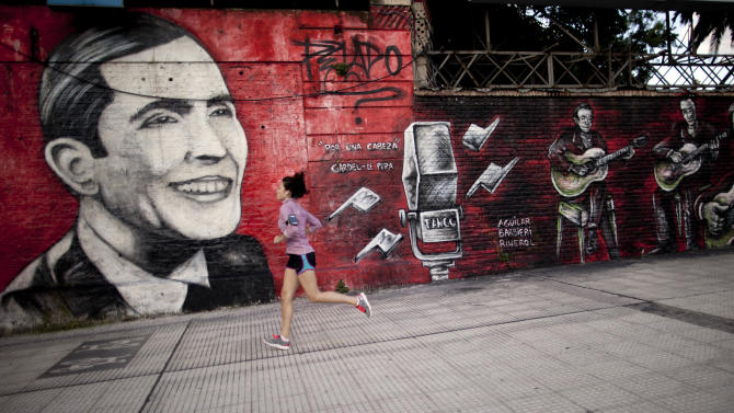 """In this March 5, 2013 photo, a woman jogs past a mural of singer and composer Carlos Gardel titled """"Por Una Cabeza"""" by artist Pelado in the Palermo neighborhood of Buenos Aires Argentina. While it's illegal to paint on the side of a building in the public right of way without an owners' permission, artists can do pretty much as they please with an owner's OK in Buenos Aires. (AP Photo/Natacha Pisarenko)"""
