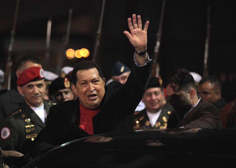 Venezuela's President Hugo Chavez waves after receiving military honors upon his arrival at the Simon Bolivar airport in Maiquetia , Venezuela, Friday March 16, 2012. Chavez returned home Friday nearly three weeks after undergoing cancer surgery in Cuba. (AP Photo/Fernando Llano)