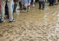 Spectators stand in the mud during the qualifying session at the Silverstone circuit on July 7 ahead of the British Formula One Grand Prix. Silverstone's managing director has vowed to carry on in his job as the circuit started counting the cost of last weekend's rain-marred race