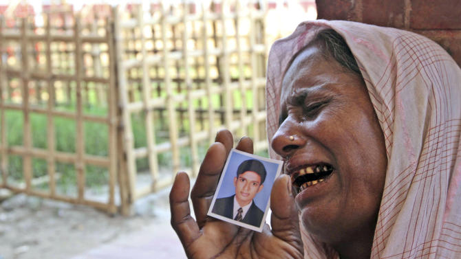 A Bangladeshi woman, holding a photo of her missing son, cries at a graveyard after a garments factory building collapse in Savar near Dhaka, Bangladesh, Friday May 3, 2013. Authorities suspended the mayor of the suburb of Savar, where the building was located, and arrested an engineer who called for the building's evacuation last week but was also accused of helping the owner add three illegal floors to the eight-story structure. (AP Photo/Palash Khan)