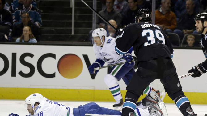 Vancouver Canucks right wing Jannik Hansen (36) slides next to San Jose Sharks center Logan Couture (39) during the second period of Game 4 of their first-round NHL hockey Stanley Cup playoff series in San Jose, Calif., Tuesday, May 7, 2013. (AP Photo/Marcio Jose Sanchez)