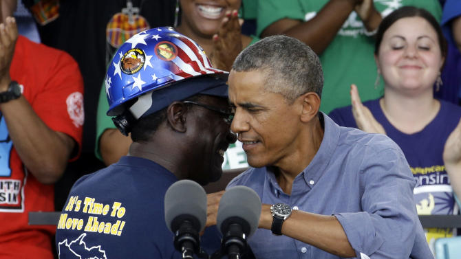 President Obama hugs Chris Harris, Vice President of United Steel Workers Local 2-209, after being introduced at Laborfest 2014 at Henry Maier Festival Park Monday, Sept. 1, 2014, in Milwaukee. Obama renewed his call for an increase in the minimum wage. (AP Photo/Morry Gash)
