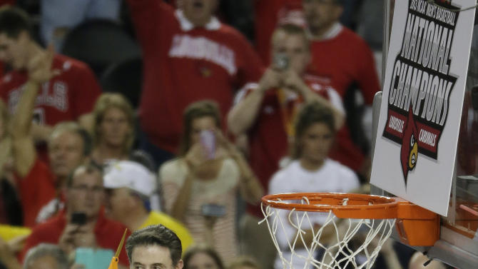 Louisville head coach Rick Pitino prepares to cut  a piece of the net after the team defeated Michigan 82-76 during the NCAA Final Four tournament college basketball championship game, Monday, April 8, 2013, in Atlanta.  (AP Photo/Chris O'Meara)