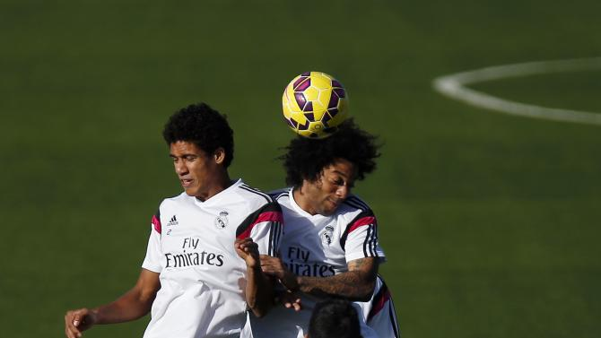 "Real Madrid's Varane and Marcelo jump to head the ball during their training session on the eve of their Spanish first division ""Clasico"" soccer match against Barcelona in Madrid"