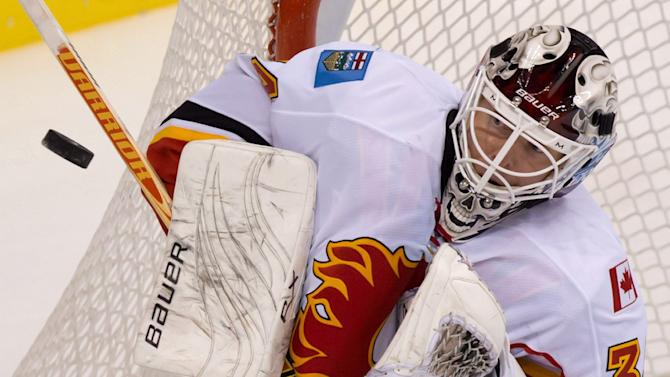 FILE - In this Jan. 23, 2013 file photo, Calgary Flames' goalie Miikka Kiprusoff, of Finland, makes a save against the Vancouver Canucks during the third period of an NHL hockey game in Vancouver. Kiprusoff is retiring from the NHL after 12 seasons. Kiprusoff says he made the decision to retire at the end of last season, but wanted to think about it over the summer before making an official announcement on Monday, Sept. 9, 2013. (AP Photo/The Canadian Press, Darryl Dyck)